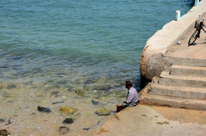 O homem mergulha os pés na água no cais da praia perto das etapas em Jaffna Sri Lanka fotos de stock
