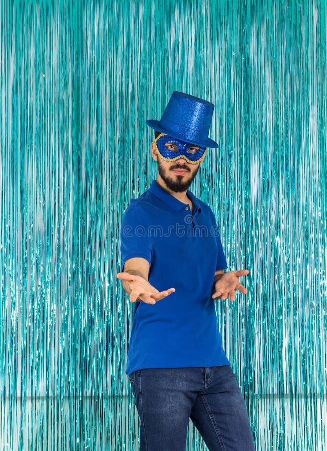 O homem misterioso faz a pose O brasileiro está vestindo a roupa azul: a imagem de stock