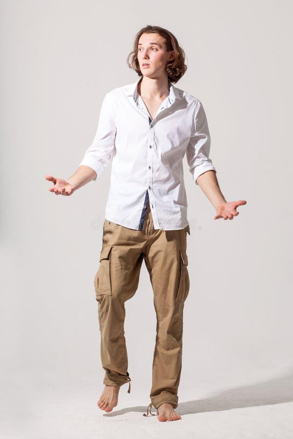 O homem modelo masculino caucasiano novo joga acima as mãos fotografia de stock royalty free