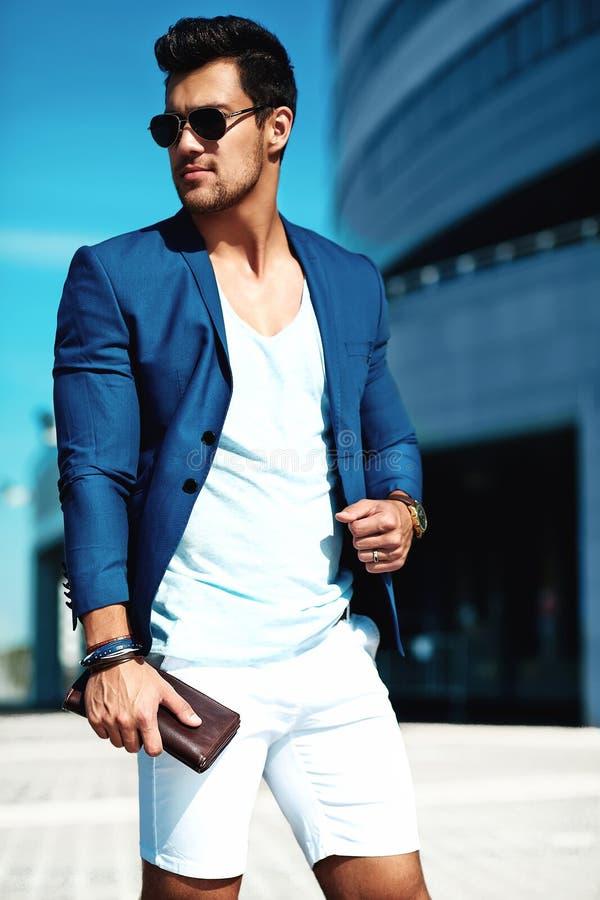 O homem modelo vestiu-se no terno elegante que levanta no fundo da rua foto de stock