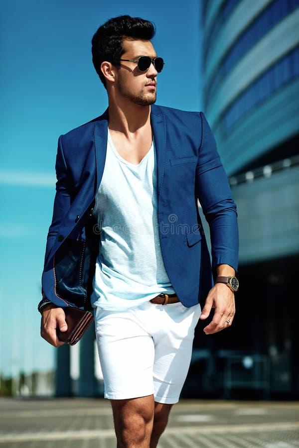 O homem modelo vestiu-se no terno elegante que levanta no fundo da rua fotografia de stock