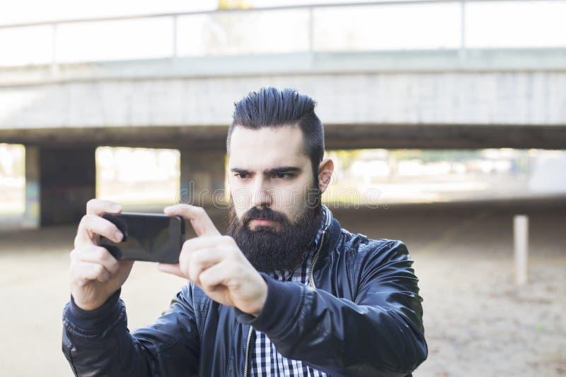 O homem moderno atrativo do moderno faz um selfie imagem de stock