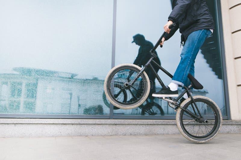 O homem monta uma bicicleta na roda traseira de um BMX contra uma janela de vidro da loja Um adolescente faz truques em uma bicic foto de stock
