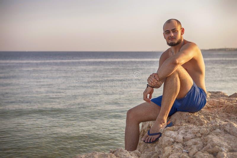 O homem moreno do ajuste magro 'sexy' no roupa de banho azul aprecia as férias, stan fotografia de stock royalty free