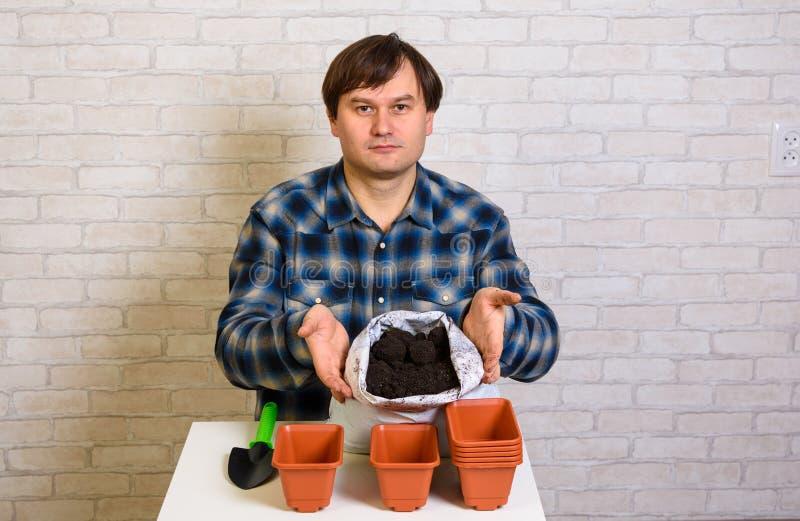 O homem mostra o solo no saco para plântulas fotos de stock royalty free