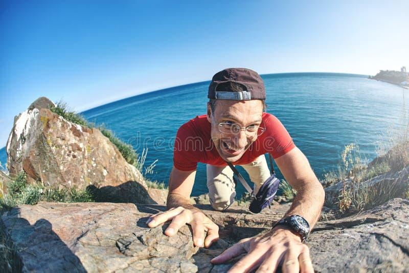 O homem mostra uma escalada pesada em uma rocha imagem de stock