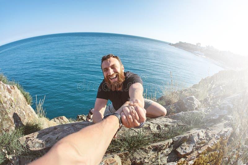 O homem mostra uma escalada pesada em uma rocha imagens de stock royalty free