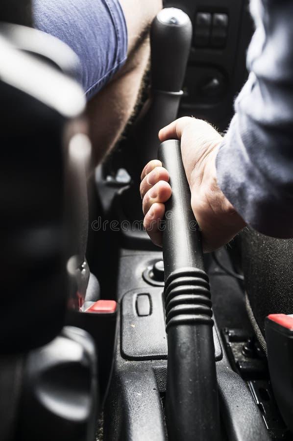 O homem - o motorista guarda o handbrake no carro fotografia de stock royalty free
