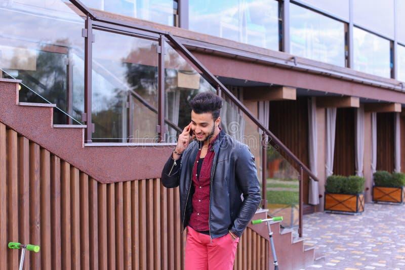 O homem muçulmano eficiente bonito vai e fala pelo telefone e pelo S foto de stock
