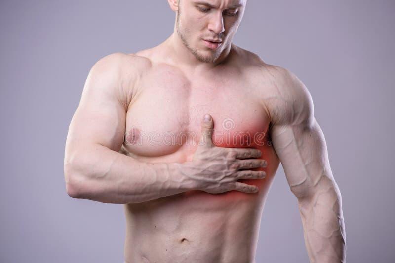 O homem muscular atlético tem a dor no coração Vermelho imagens de stock royalty free