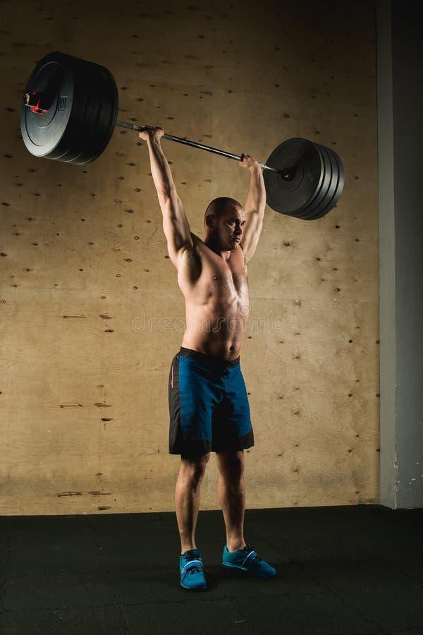 O homem muscular brutal com o trem da barba com barbell aumentou em cima no gym fotografia de stock royalty free