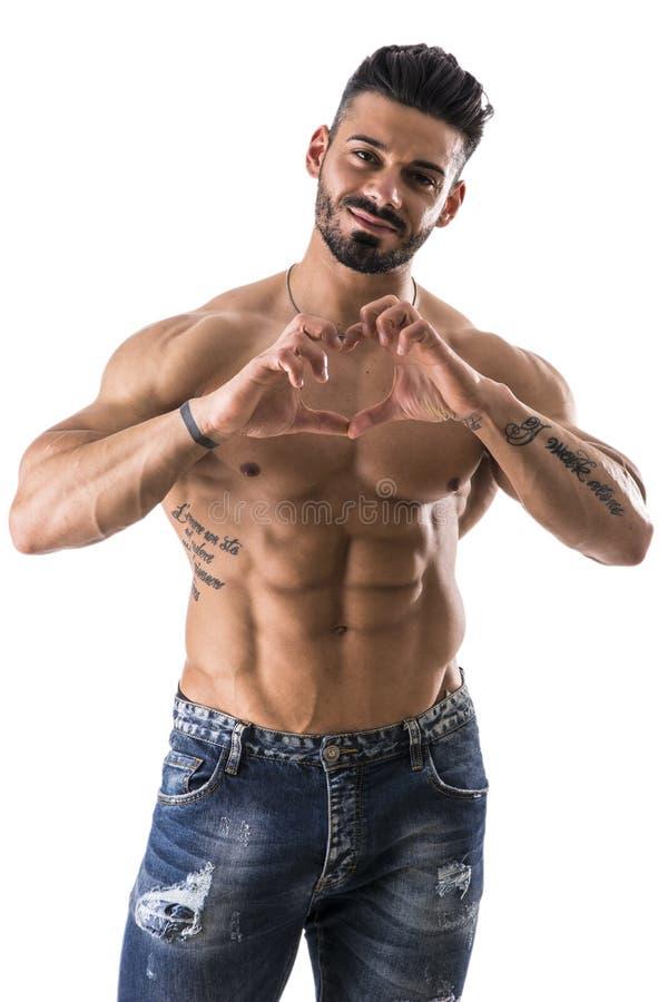 O homem muscular descamisado que faz o coração canta com mãos imagens de stock royalty free