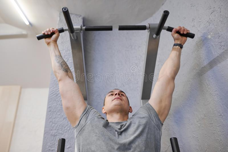 O homem muscular forte novo no gym, exercício do homem, fazendo a tração levanta imagens de stock royalty free