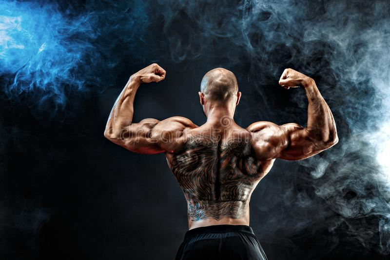 O homem muscular irreconhecível com tatuagem suporta sobre contra do fundo preto Isolado foto de stock