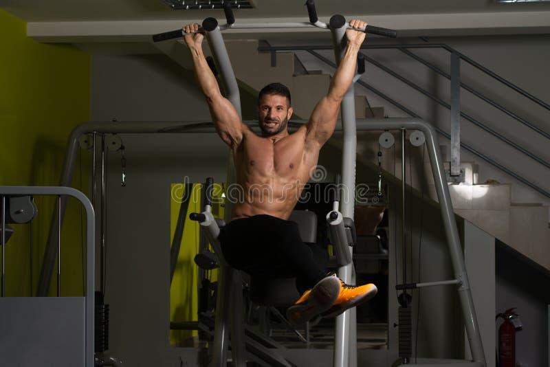 O homem muscular que executa o pé de suspensão levanta o exercício fotografia de stock
