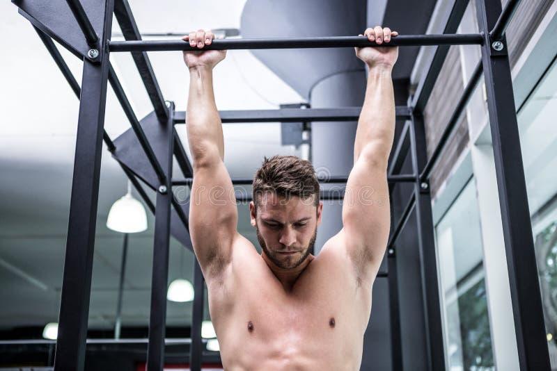 O homem muscular que faz a tração levanta fotografia de stock