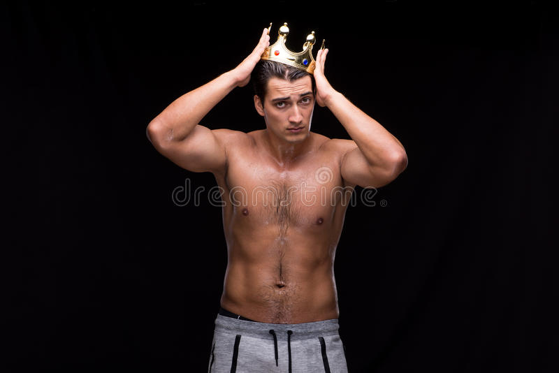 O homem muscular rasgado com coroa do rei fotografia de stock