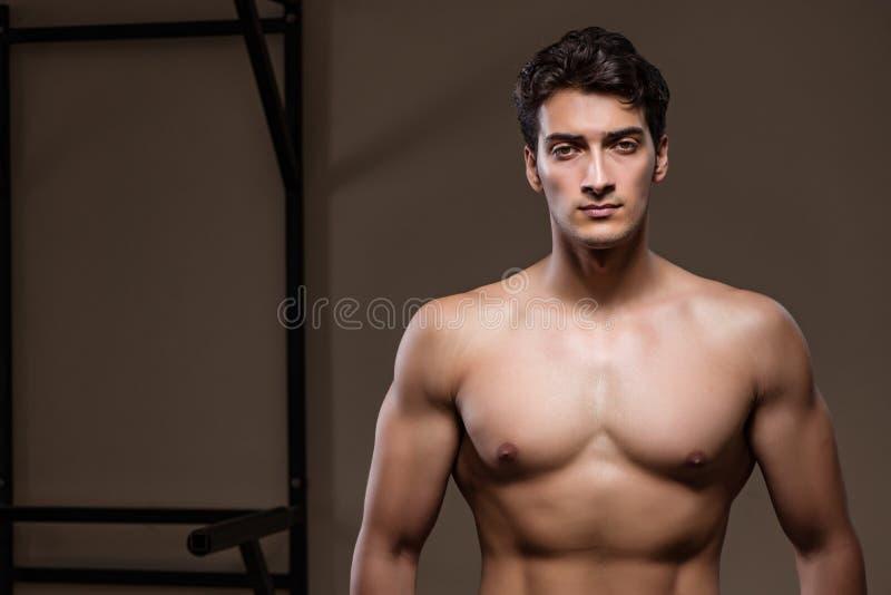 O homem muscular rasgado no gym que faz esportes fotografia de stock royalty free