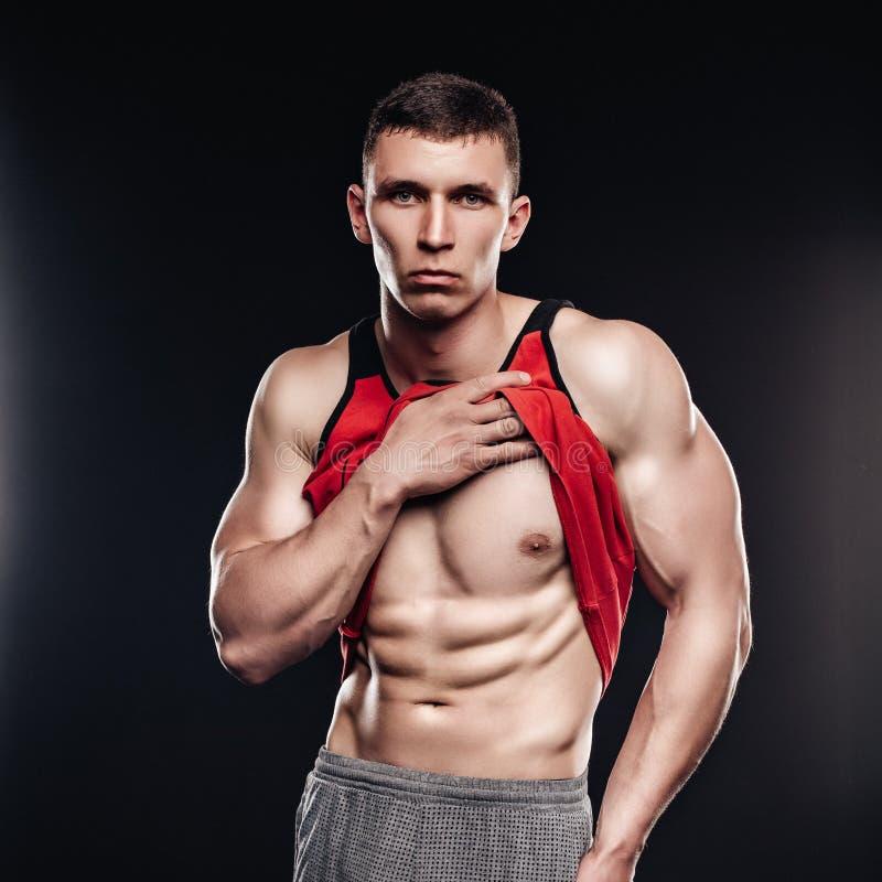 O homem muscular 'sexy' da aptidão que mostra o sixpack muscles sem gordura sobre o fundo preto Modelo atlético forte da aptidão  imagens de stock royalty free