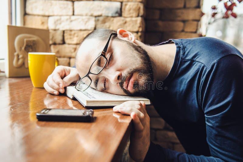 O homem não barbeado nos vidros cansados, caiu adormecido na tabela imagem de stock