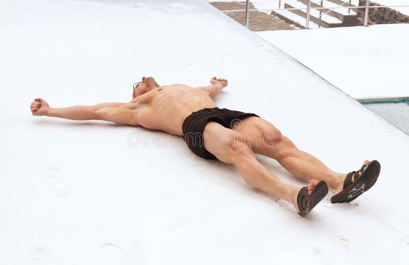 O homem não está receoso do frio e não se encontra no short no inverno na neve imagem de stock royalty free