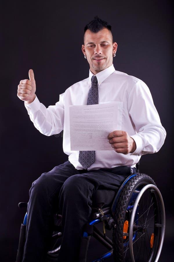 O homem na cadeira de rodas é bem sucedido imagens de stock royalty free