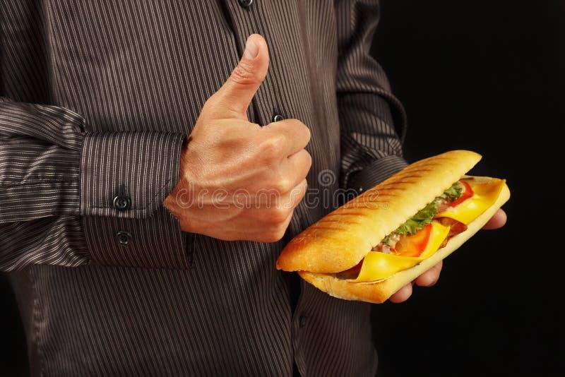 O homem na camisa preta recomenda e gosta do cheeseburger grande no fundo preto foto de stock royalty free
