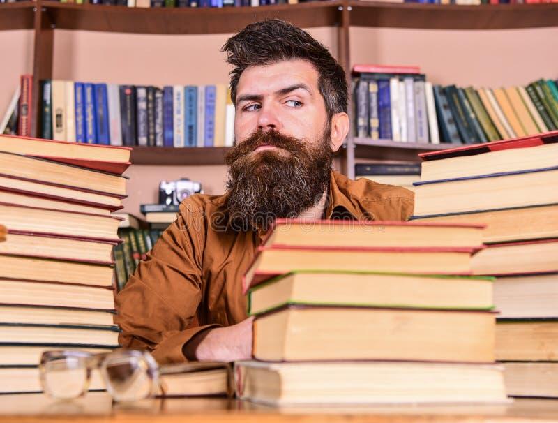 O homem na cara restrita senta-se entre pilhas dos livros, ao estudar na biblioteca, estantes no fundo Professor ou estudante imagens de stock