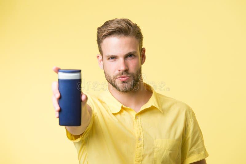 O homem na cara segura recomenda o champô, fundo amarelo O indivíduo com cerda guarda a garrafa do champô, espaço da cópia Homem foto de stock