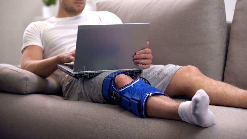 O homem na cinta de joelho da artrite que trabalha no portátil reabilita em casa o período e autônomo foto de stock royalty free