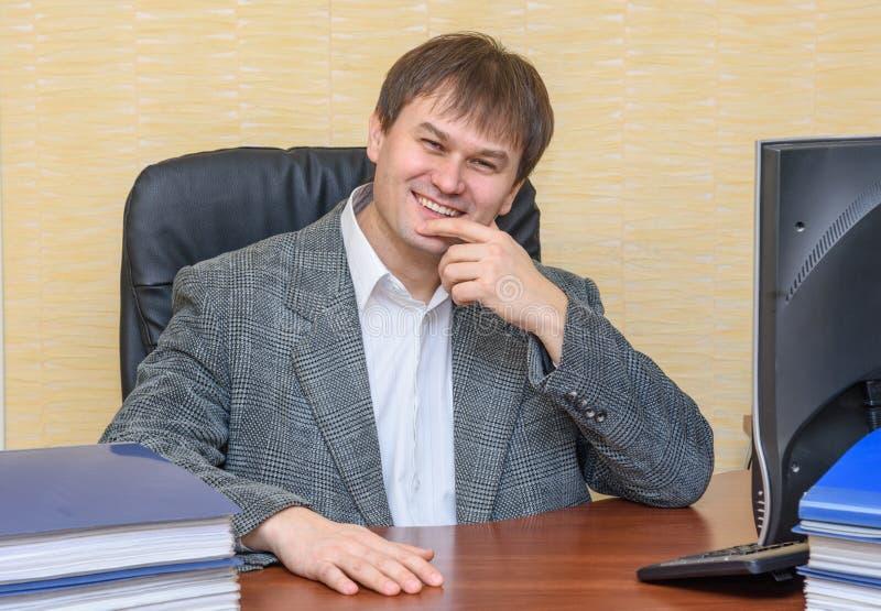 O homem na mesa no escritório que sorri felizmente fotos de stock royalty free