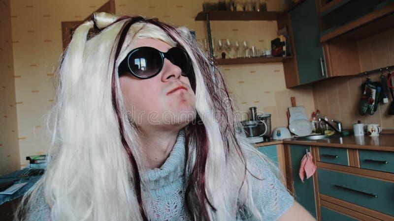 O homem na peruca do ` s da mulher nos óculos de sol come a maçã na tabela parody Cabelo do toque chewing vídeos de arquivo