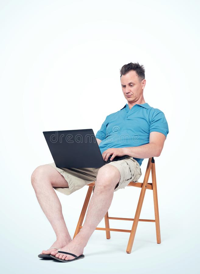 O homem na roupa do verão está sentando-se em uma cadeira, datilografando em um portátil Fundo claro Conceito do trabalho em féri fotografia de stock royalty free