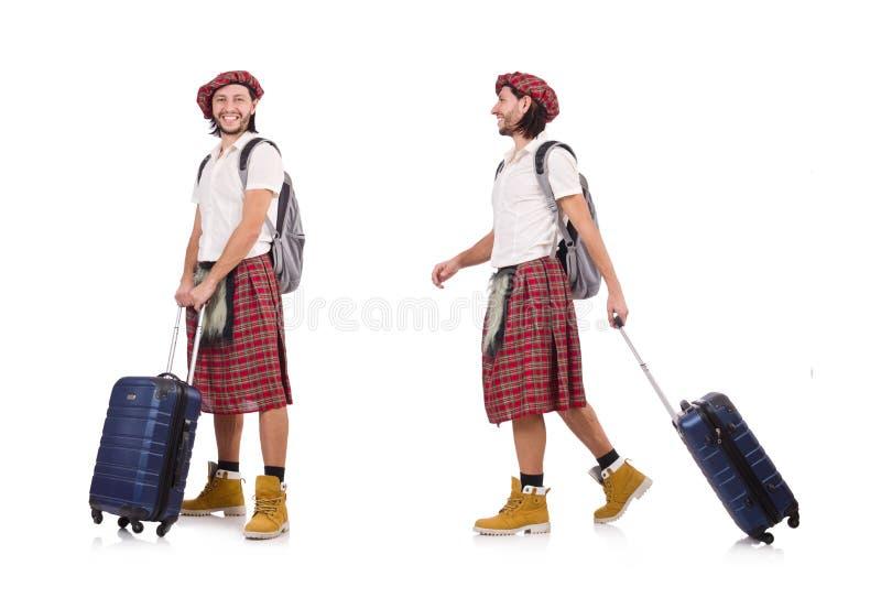 O homem na saia do scottish com a mala de viagem isolada no branco fotografia de stock