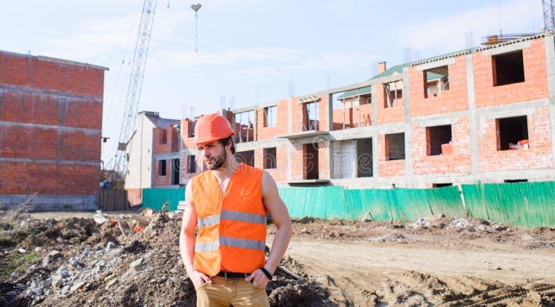 O homem na veste e no capacete alaranjados trabalha no canteiro de obras Conceito das responsabilidades do contratante Indivíduo  imagens de stock royalty free