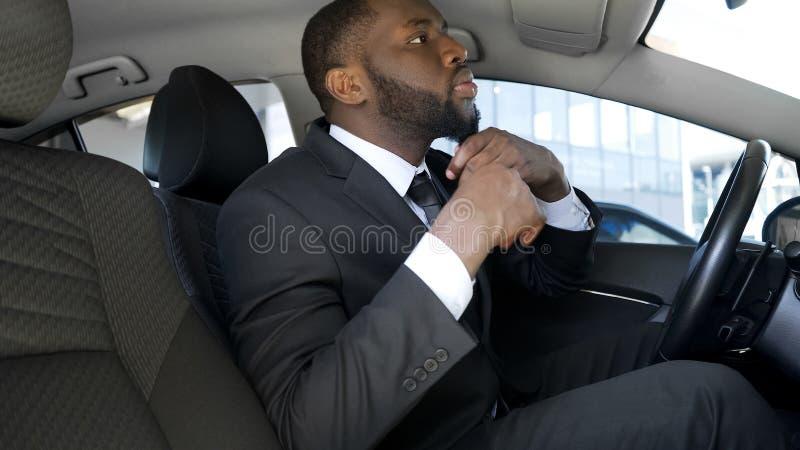 O homem negro considerável no terno de negócio que olha no espelho de carro, apronta-se para a data imagens de stock royalty free