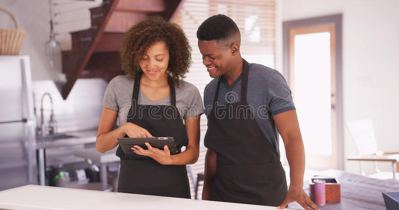 O homem negro e a mulher planeiam sua receita em sua tabuleta fotos de stock