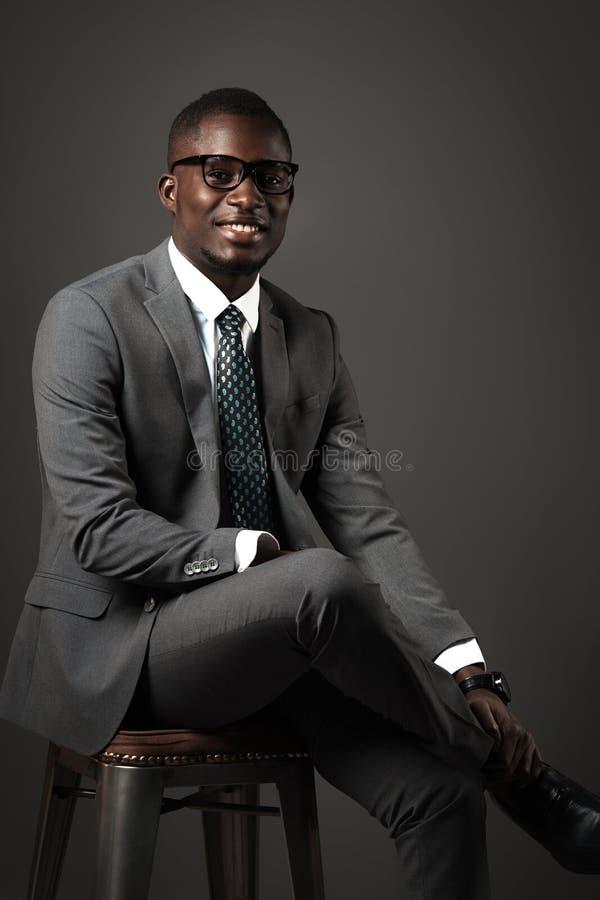 O homem negro novo de sorriso senta-se com vidros e o terno de negócio cinzento foto de stock royalty free