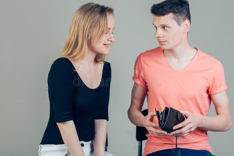 O homem Nerdy está tentando esconder o dinheiro de sua esposa porque quer o gastar todo fotografia de stock