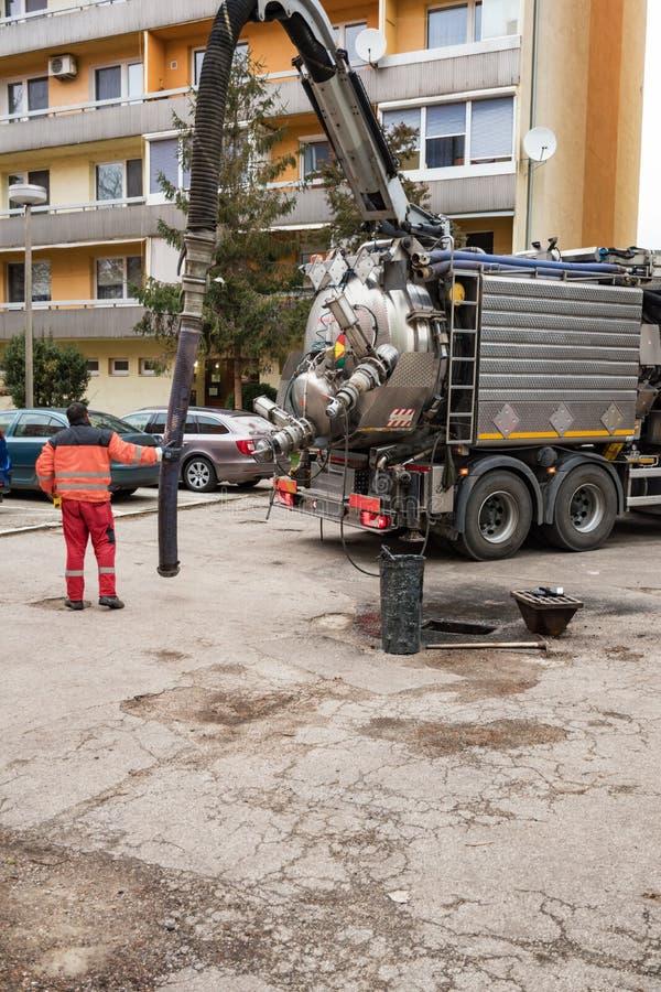 O homem no boilersuit está bombeando a água de esgoto com água de esgoto da sução da drenagem imagem de stock