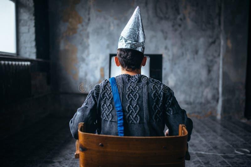 O homem no capacete do papel de alumínio olha a tevê, fobia do UFO fotografia de stock