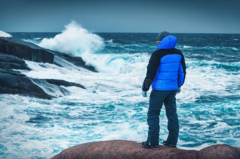 O homem no casaco azul está estando na pedra na costa de mar foto de stock