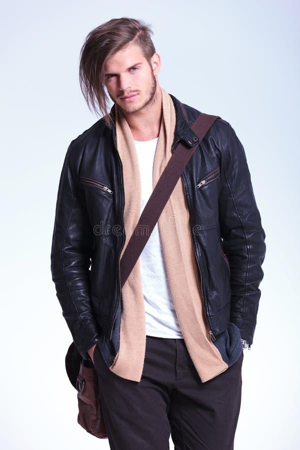 O homem no casaco de cabedal está estando com mãos em uns bolsos e em um smil imagens de stock