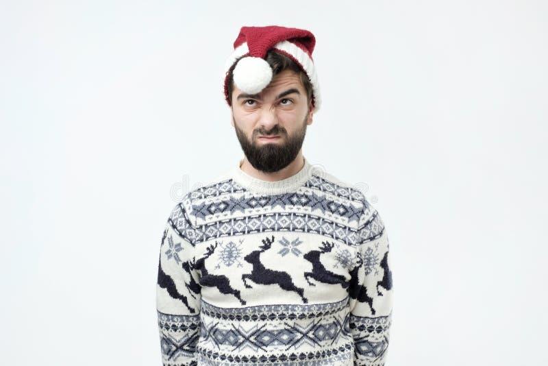 O homem no chapéu vermelho do Natal olha de sobrancelhas franzidas cara com descontentamento, irritou a expressão, sendo desconte imagem de stock royalty free