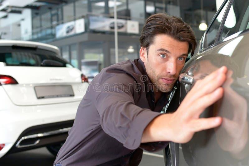 O homem no concessionário automóvel olha um veículo na sala de exposições fotografia de stock