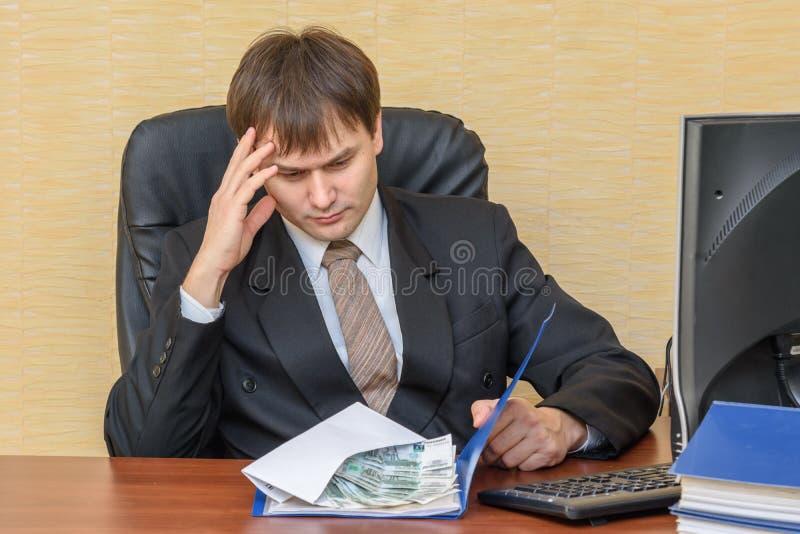 O homem no escritório, pensando olhando o dinheiro, que se encontra em um dobrador fotos de stock royalty free