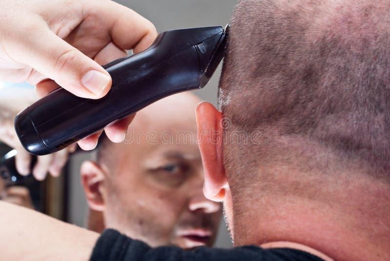 O homem no espelho corta seu cabelo imagem de stock