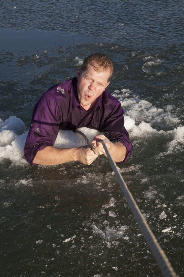 O homem no furo do gelo retira no frio da corda imagem de stock royalty free