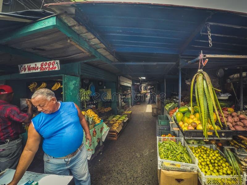 O homem no mercado do vegetal e de fruto está no mercado do alimento no stree fotografia de stock
