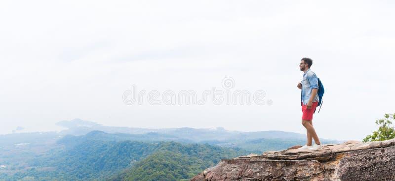 O homem no pico de montanha que levanta as mãos com trouxas aprecia o conceito da liberdade da paisagem, Guy Tourist novo imagem de stock royalty free